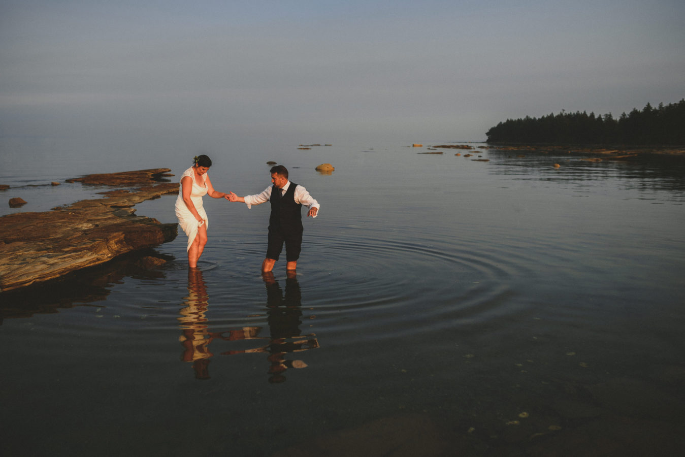 an older bride and groom wading in the ocean on their wedding day