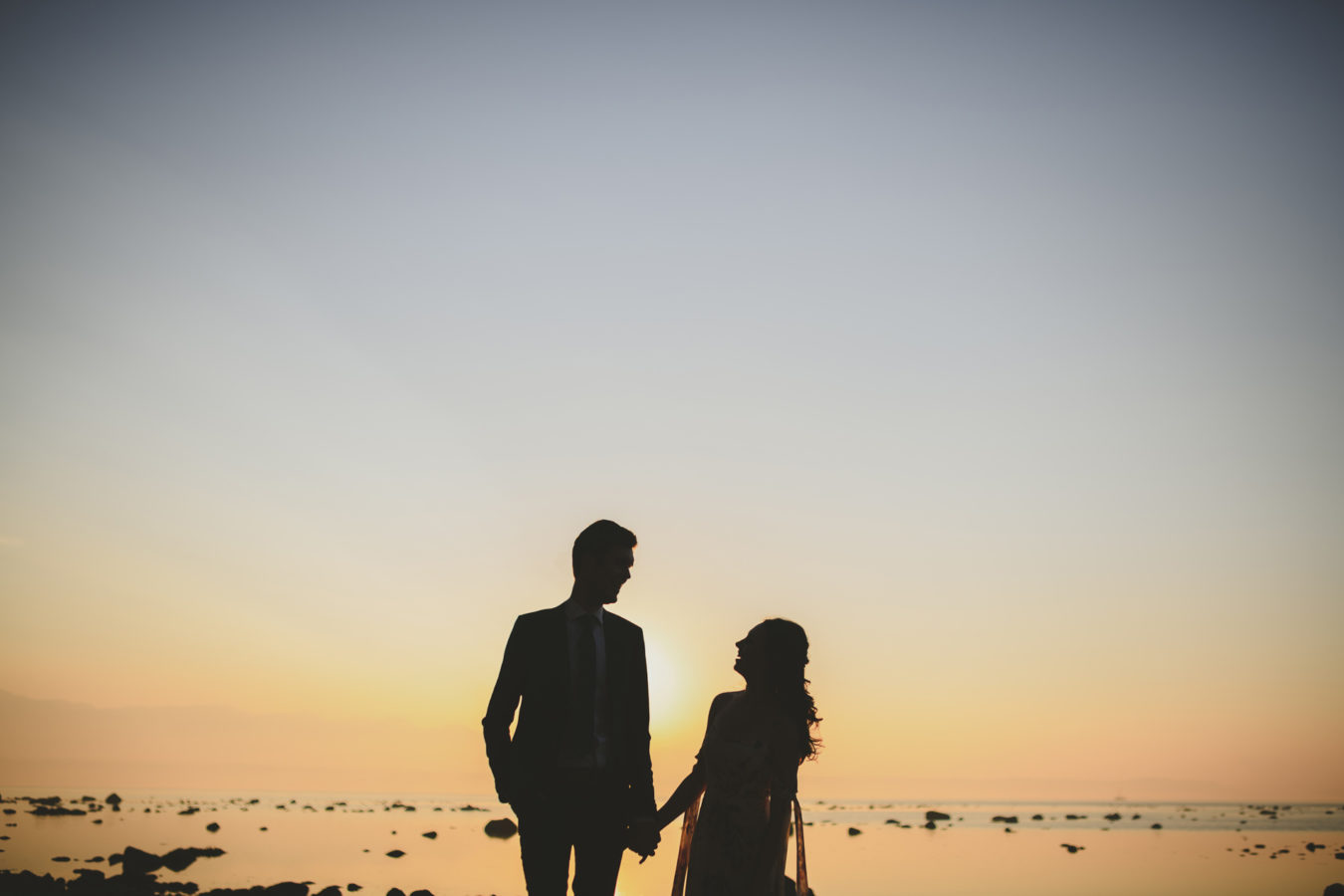 wedding couple silhoutted against the sunset at the ocean's edge