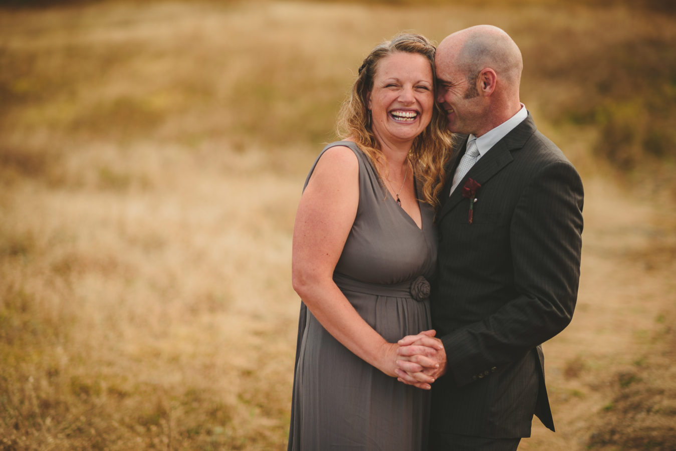 wedding couple laughing while embracing in a grassy field