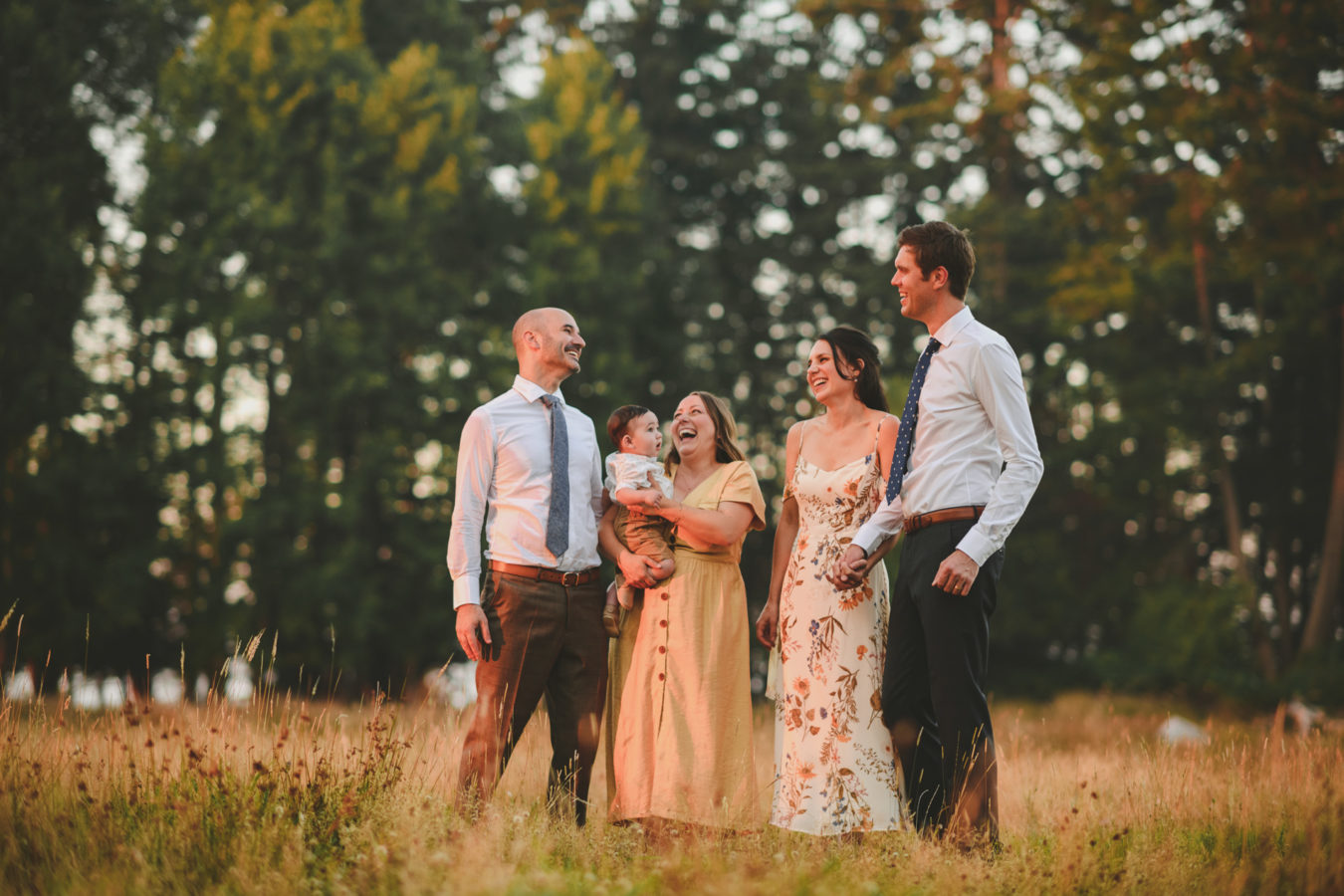 bride, groom and their 2 friends and a baby laughing in a field with the forest behind them