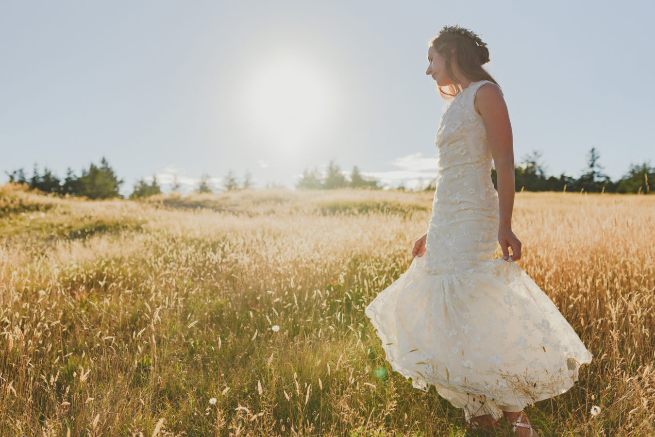 bride spinning in her wedding dress in a grassy field with the sunshine behind her