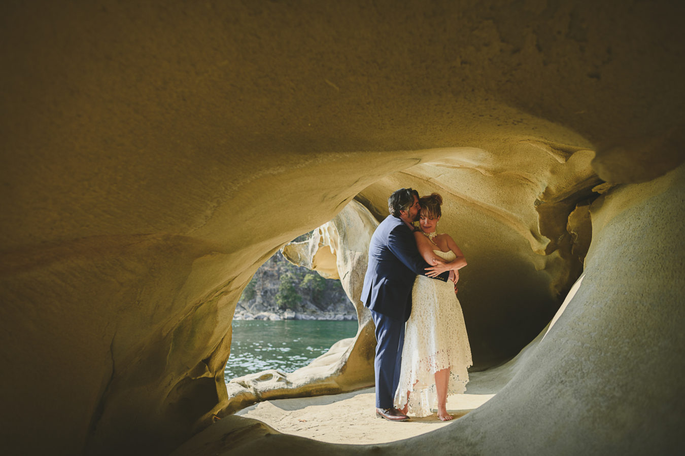 older bride and groom snuggled in a sandstone cave by the ocean's edge