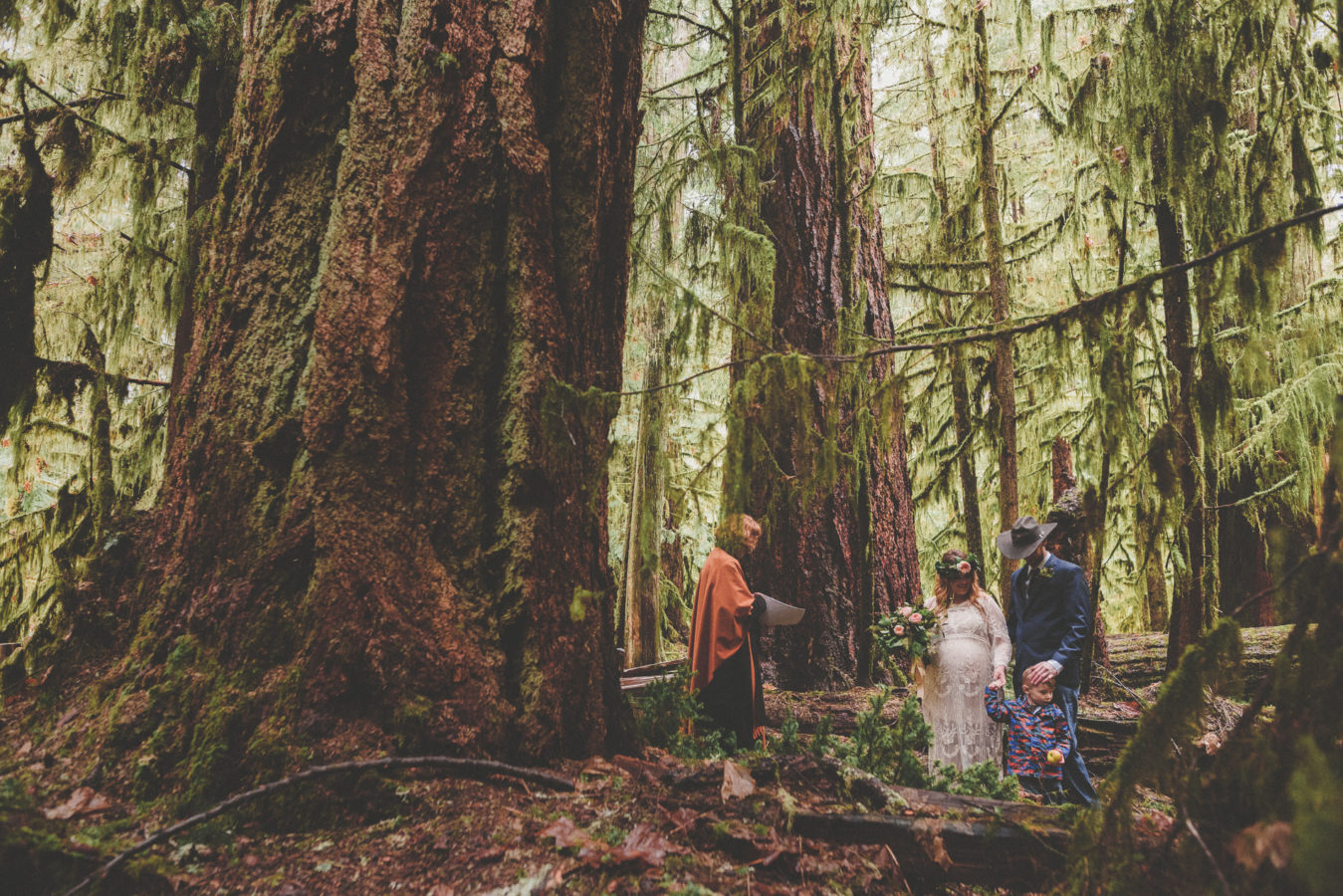 bride, groom, their young son and officiant getting married in the old growth forest