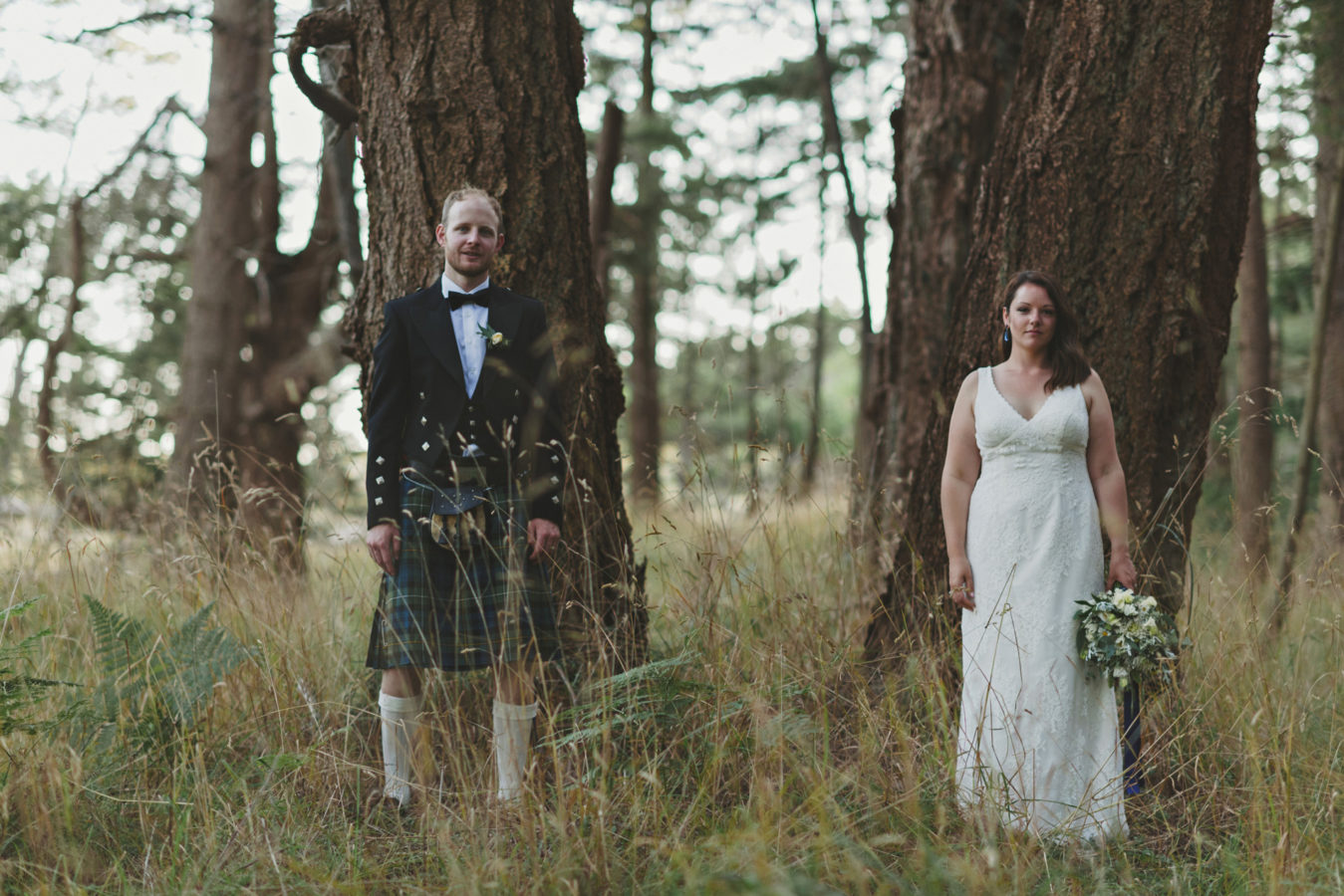 bride and groom each standing against an old growth tree looking deadpan into the camera