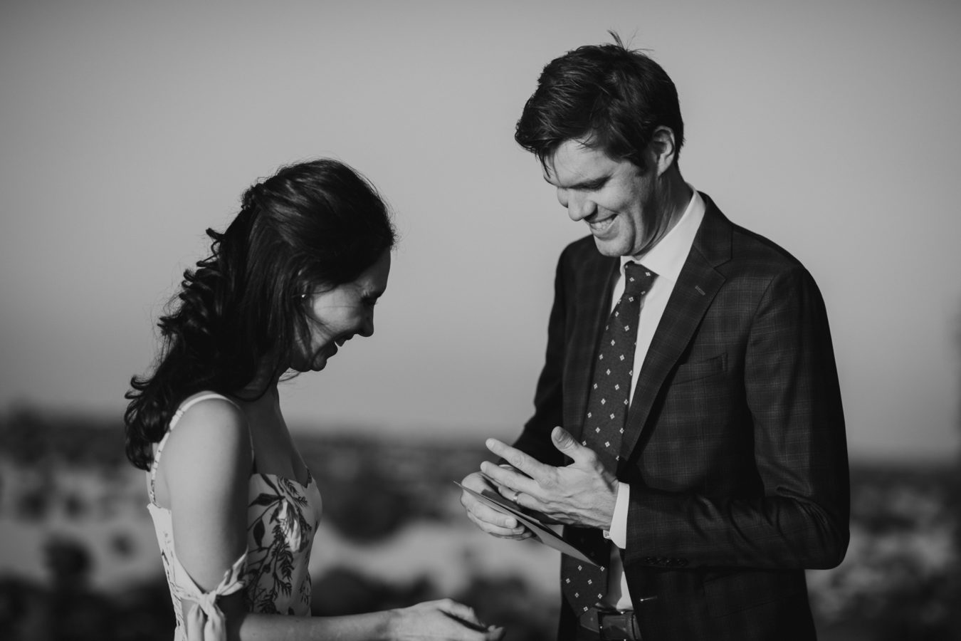 bride and groom laughing at their elopement as he tries to get his ring on his finger