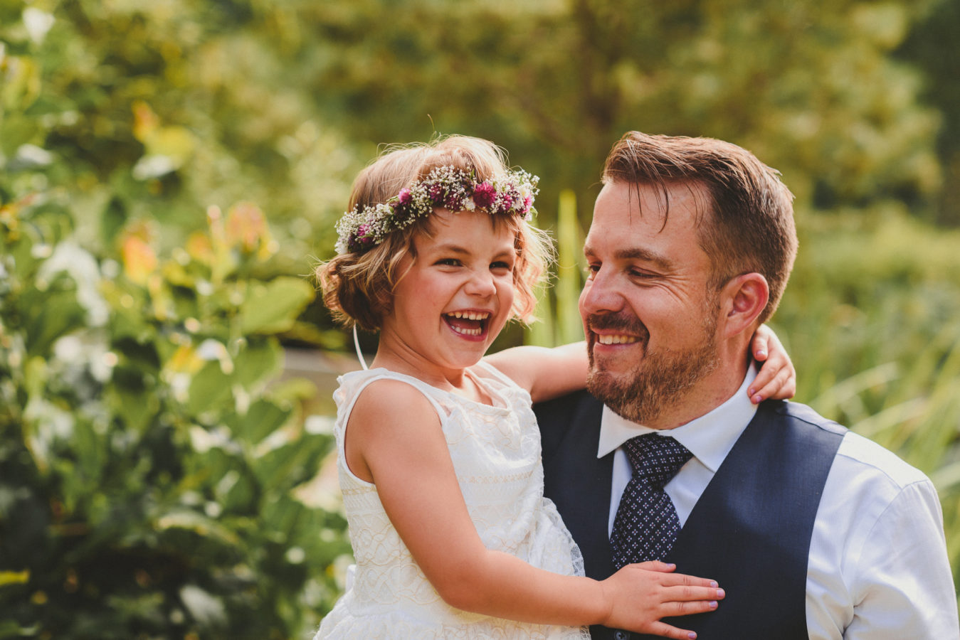 groom holding his daughter while she's laughing at his wedding