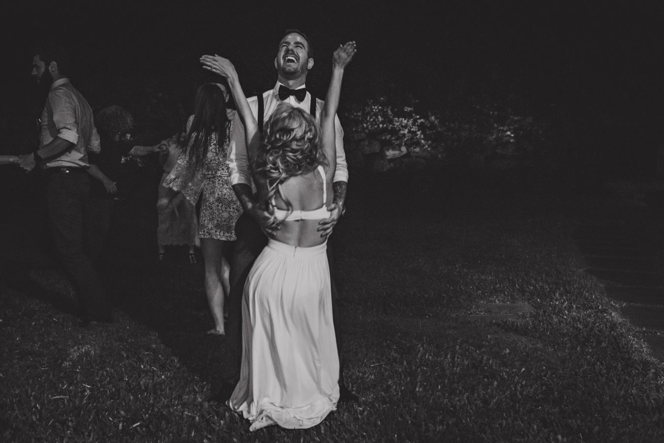 bride and groom dancing in a dark yard on their wedding day while he's throwing his head back laughing