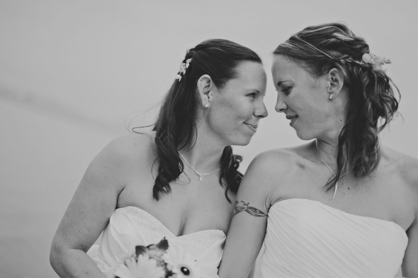 two brides in wedding dresses intimately looking at one another