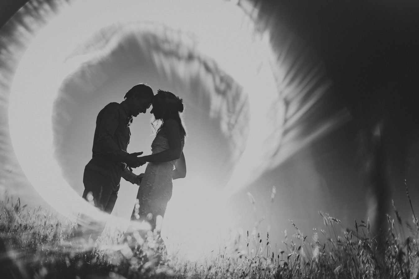 bride and groom holding hands in a grassy field with a ring of light surrounding them
