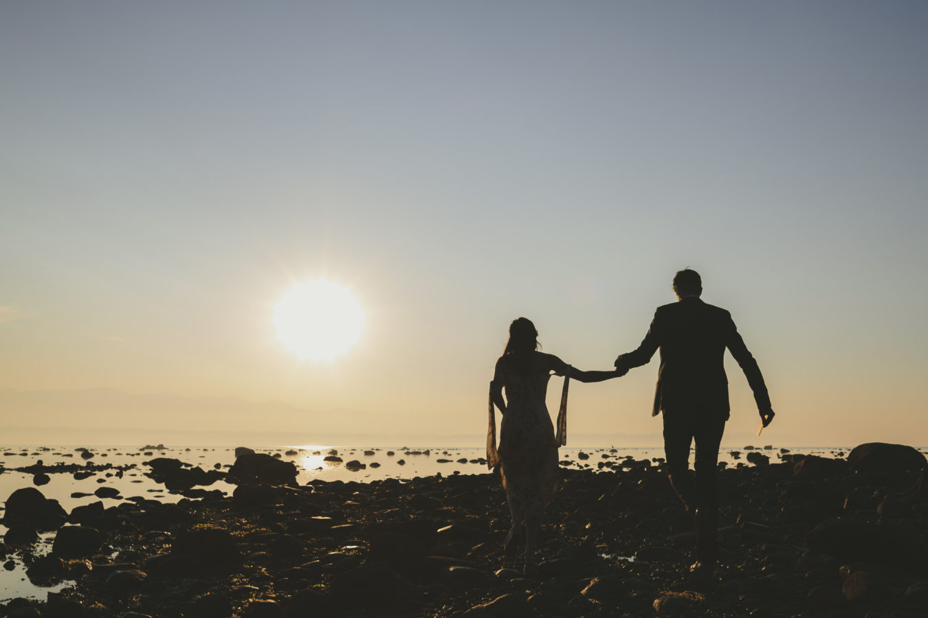couple holding hands walking along a rocky beach silhouted by the sunset