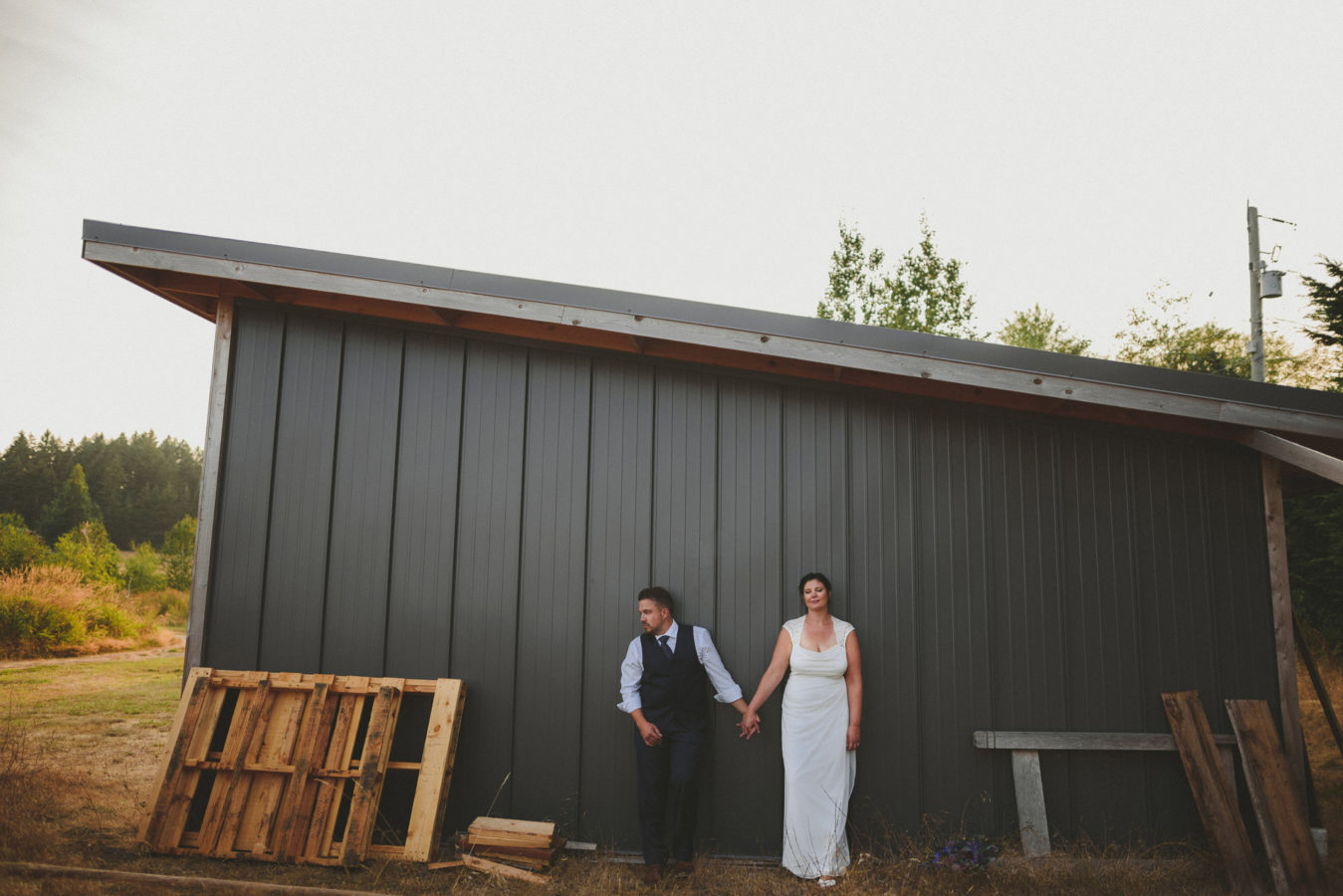 bride and groom leaning against a metal sided out building in a field on their wedding day