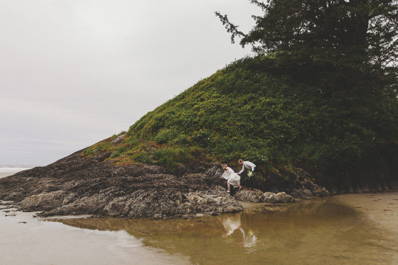 bride and groom clambering on a rocky bluff at the ocean's edge with their refection in the still water below them