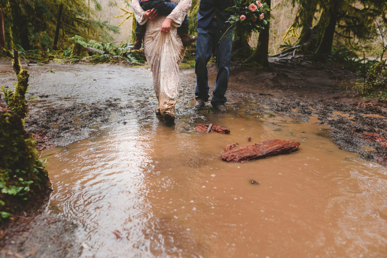 bride and groom walking together into a big mud puddle on a path in the forest on their wedding day while she holds their young child in her arms