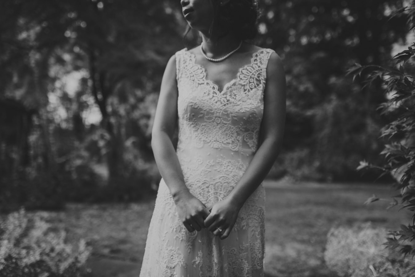 close up of a bride standing in the forest on her wedding day