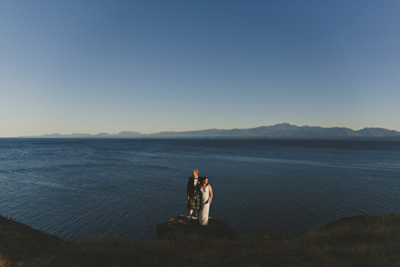bride and groom on a rocky outcropping on a cliff overlooking the ocean