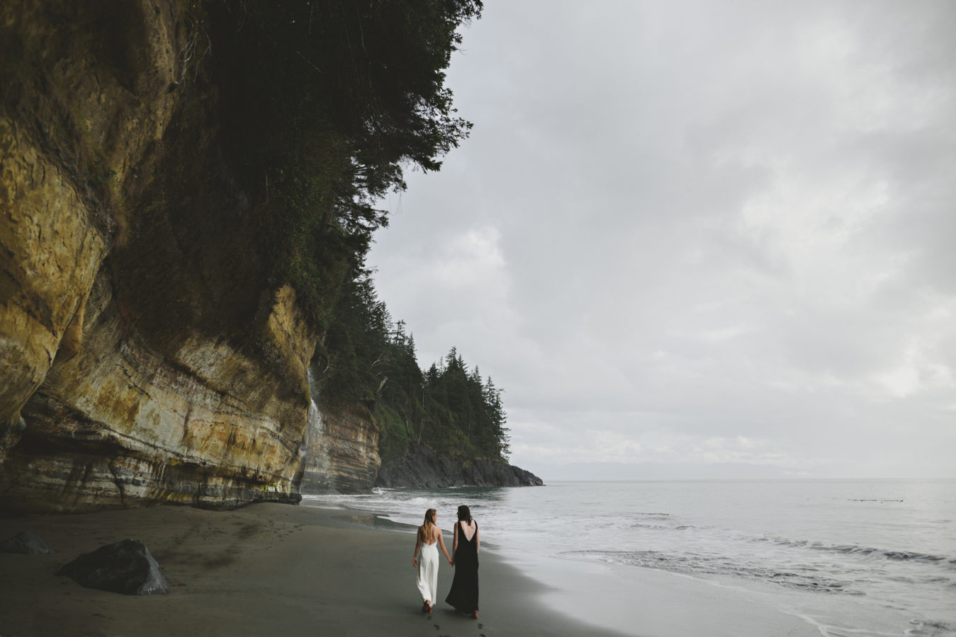 two brides walking down the edge of a beach towards a waterfall at the cliff's edge